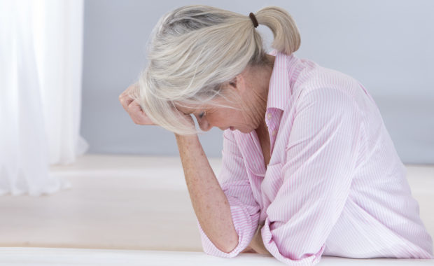 Farewell to Stress - Woman with head down, hand on forehead